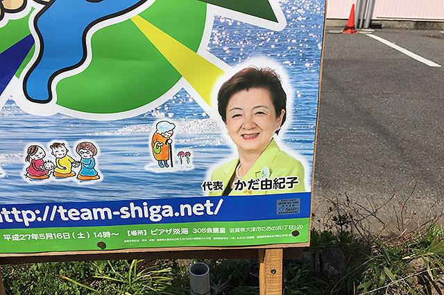 チームしがのポスターの右下には嘉田さん。ちゃんと緑色のジャケットを着ている。