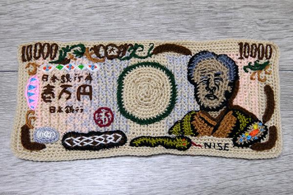 コピーすることが禁止されている紙幣。ならば、と毛糸で編みました。出来もいいしその執念と技術には恐れ入りますが、急にヘビとか編みこんじゃったのがほんと謎。(安藤)