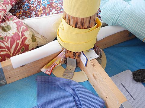 ツーバイフォー材を十字に組んで金具をとりつけている。2000円以内でできる。クッション代わりにふとんが置かれている。