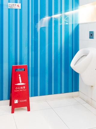 i SQUARE というショッピングモールのトイレにあった小心地滑。人の形が「i」になっている。わかりづらいと思ったのか、よく見ると壁には通常の滑りやさんが貼られている。