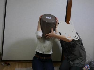 バケツが取れない呪いにかかった娘と外そうとする母の図(イメージ)