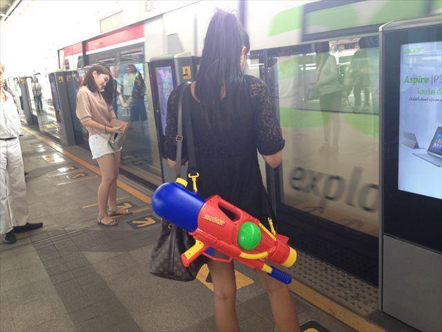 電車移動中に見かけたお姉さん、ガッツリ水鉄砲を抱えながら本を読んでいる。