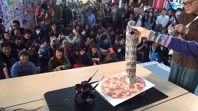 As the match starts, TSUKUBOT No. 4 approaches the tower. The iPhone installed on the top of the tower is receiving a call from the creator's friend in the audience, inviting its opponent to climb onto the pizza.