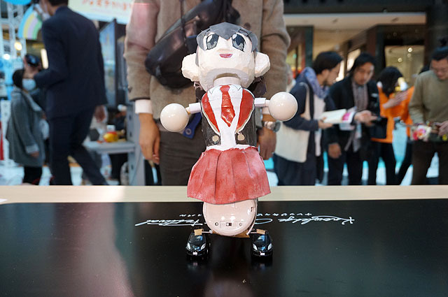 A modified dancing flower toy, she debuts as an idol who moves in response to the audience cheers.