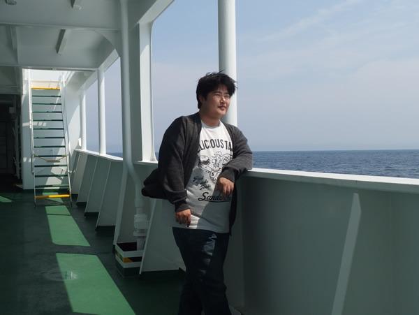 昭和のスターっぽい立ち方をしているが、ものすごい船酔いをしている。