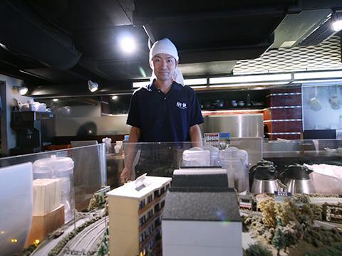 駒鉄の廣松さん。ジオラマ越しだと巨人に見えるが普通の店員さんだ。