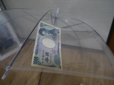 ビニール傘(200円)の裏側にひたすら千円札を貼る作業