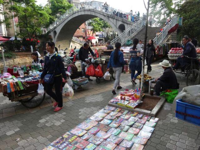 市場の近くの路上で本や100円ショップで売られてそうな雑貨がならべられていた。 焼き芋屋もあればりんご売りもいる。