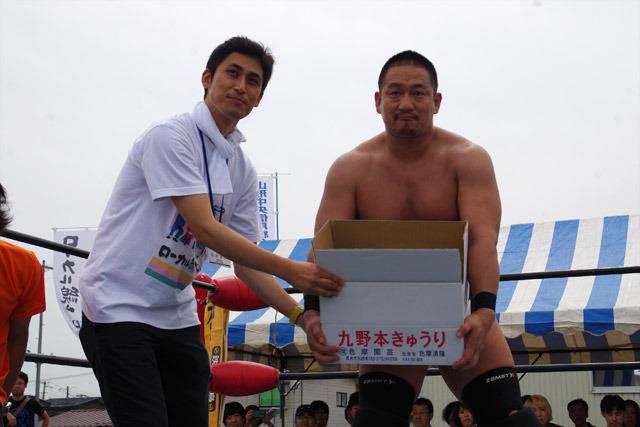勝利者賞の九野本きゅうりを高木大社長に渡す渋谷君。他にも山盛りの名産品が贈られた。