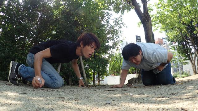 地面のにおいを懸命に嗅ぐ、2人の大人。