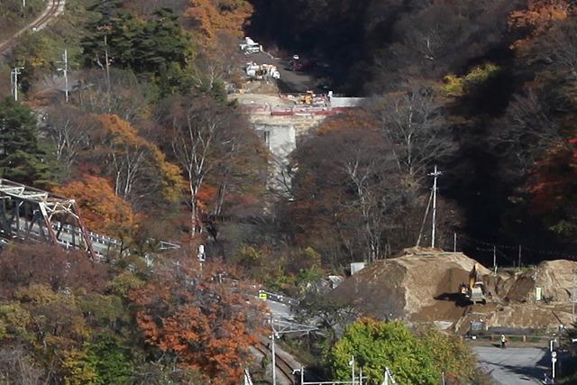 正面の木々の陰にトンネル入口、その奥で川を横切っているのが堤防、車が停まっているあたりがダム本体予定地