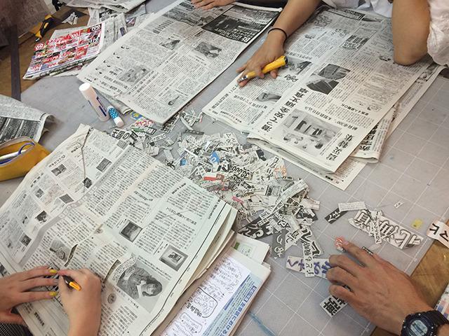 大きな作業台に新聞紙をひろげ、カッターで切り抜く。