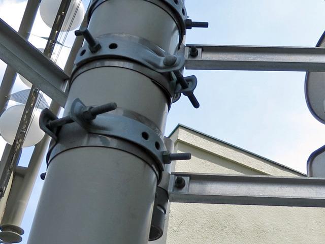 太い円柱の電柱に細長いアームを固定するための部分