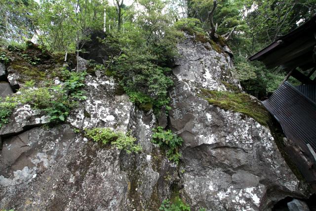 山小屋の横には巨大な岸壁が。神が宿る御座石として祀られていたそうだ