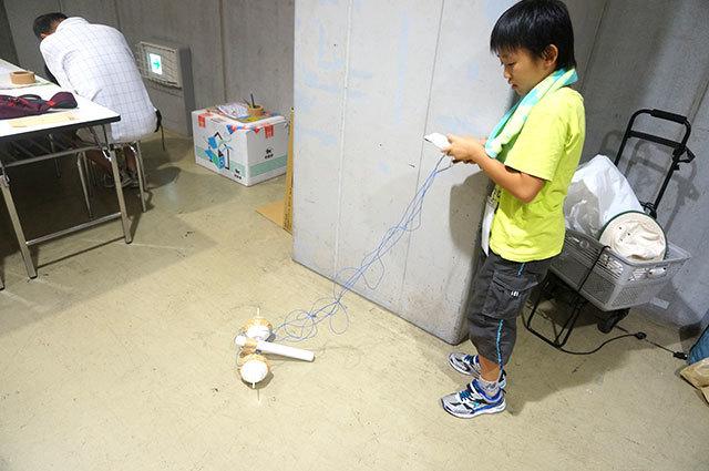 主に紙筒と食品トレイで構成されたロボット。ロボット自体の手作り感もいいけど、注目は自作リモコンである。