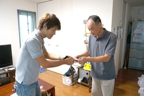 父に名刺を渡す同僚。なんだこの写真