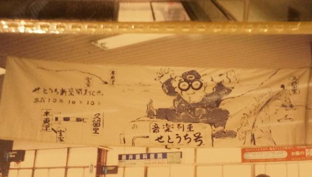 駅構内に掲出された企画列車の横断幕。ファンキーな笑顔の瀬戸内氏の似顔絵は藝大の学生が描いてくれたという。