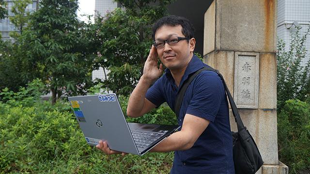 販促のプロの賢者、阿部さん。休暇でぶらっと観光気分で来たらしいが編集部古賀のパソコンを小道具として持たされてポージングさせられる @nifty WEB販促の窓口