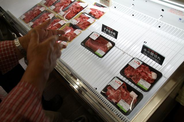 パック販売されている肉を前に、熱く語るおじいさん