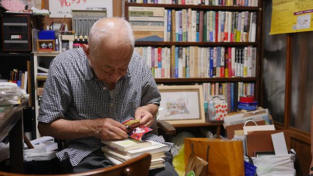 奥ではおじいさんが本に作業をしている