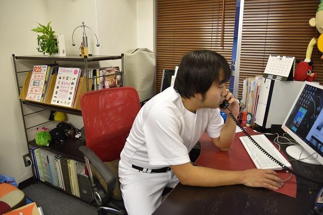 仕事の電話に対応中。週末のグラウンドを手配する草野球の監督ではありません
