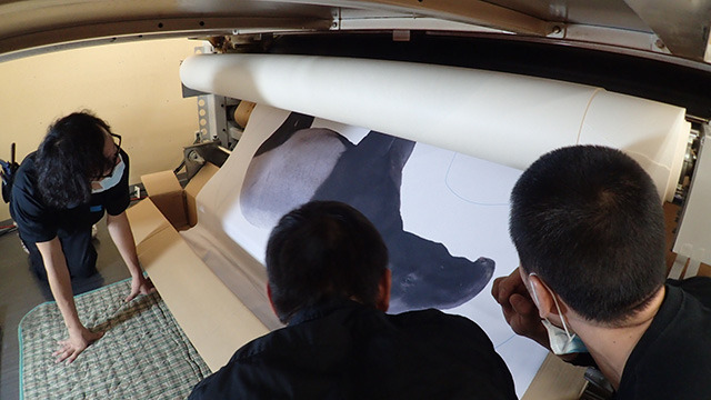 下から布に転写されたバクが出てくる。その精度を確認するスタッフのみなさん。