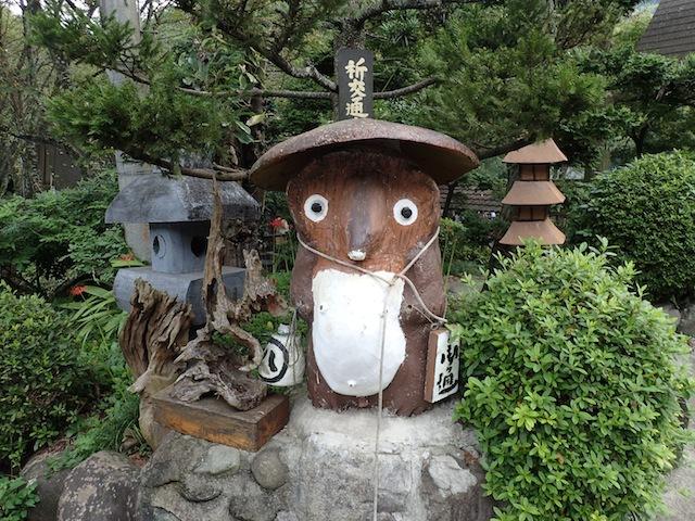 うつろでかわいいタヌキ。後ろの石灯籠もこれ木製だな…….