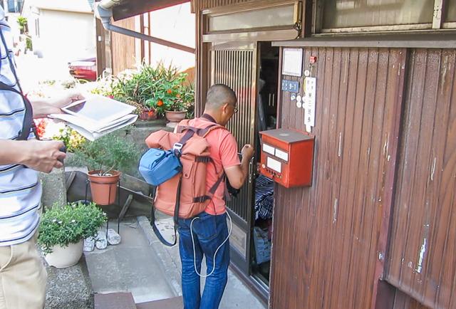 さきほどの弁天橋近くの列柱の後ろに建っているお宅の扉を叩く米野さん。えらい。すごい。見習いたい。