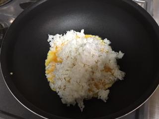 卵の上にごはんを入れて炒める。