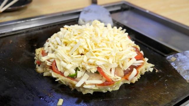 生地の上にピザソースを塗り、トマトとピーマンをトッピング。チーズを山盛りにする