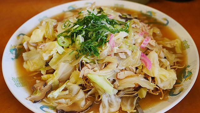 太めの揚げた中華麺に具沢山のスープがかかっている