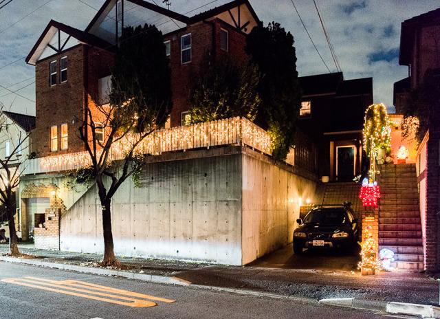道路に面したレベルはガレージ、玄関はその上。そのアプローチなどに立体感のある浮かれ電飾。