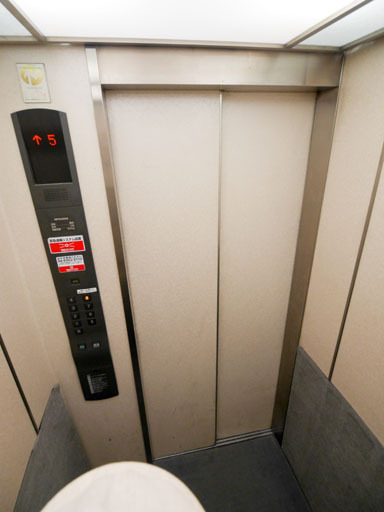 よくあるエレベータの内部。四方を壁に囲まれた空間