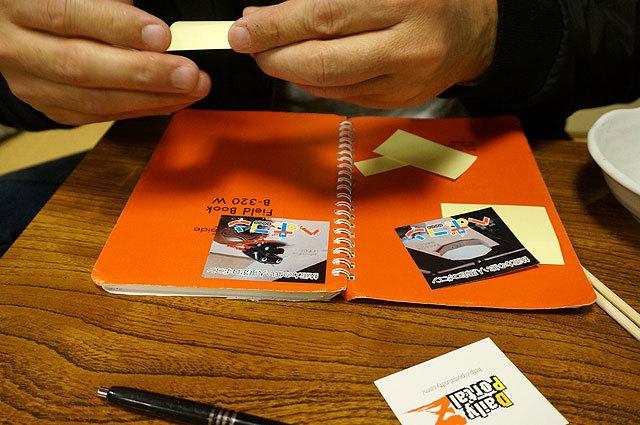 イベント前日に食事がてらインタビューを受けた時の様子。記念にあげたヘボコンシールとDPZシールをさっそく取材ノートに貼るスティーブ