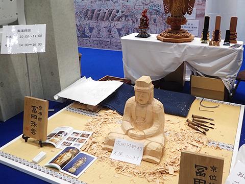 掘りかけの仏像と「次回14時より実演します」の紙。
