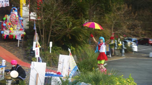派手な傘を振って呼び込みをする派手な人