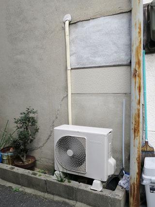 室外機から上に伸びている白い管、これが一般的なエアコン配管