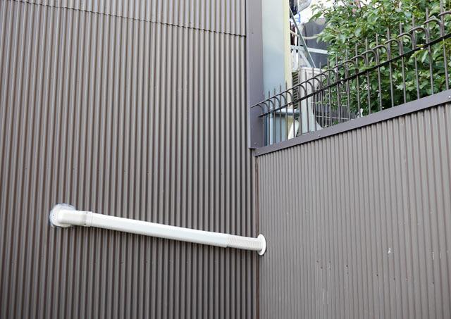 突如トタンから現れる謎の白いやつ。右上に室外機が見えることから分かるように、これもエアコン配管だ