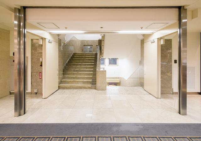 後付けであろう防火シャッターが、階段室へのゲートのように見えて、これもまたよし。