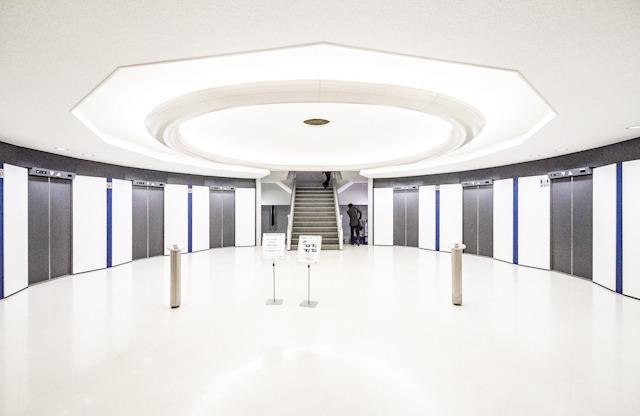 円周上にエレベーターが並ぶ。むかしのSF映画に出てきそう。そして正面に見えるのが階段室。