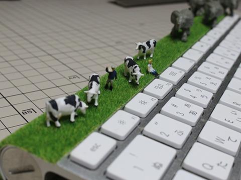危機に気付かず草を食む牛たちと、のんびりした酪農家の人フィギュア。