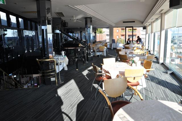 大きな窓に沿ってテーブルが置かれた2階のレストラン