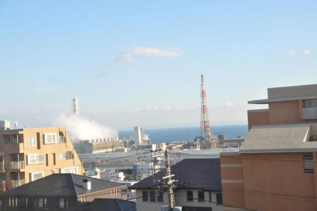 製油所の煙突越しに見える海――こんな感じだったのかな(除・マンション)