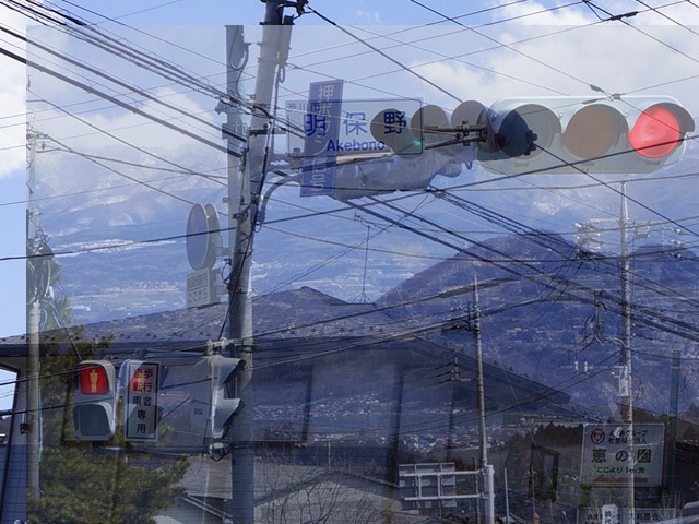 上2枚の写真を、歩行者用信号機の大きさを基準に重ねると・・・。