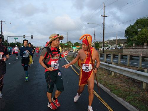 ハイタッチカウンターを付けてホノルルマラソンを走る柴山さん(とカメハメハ大王っぽい人)。