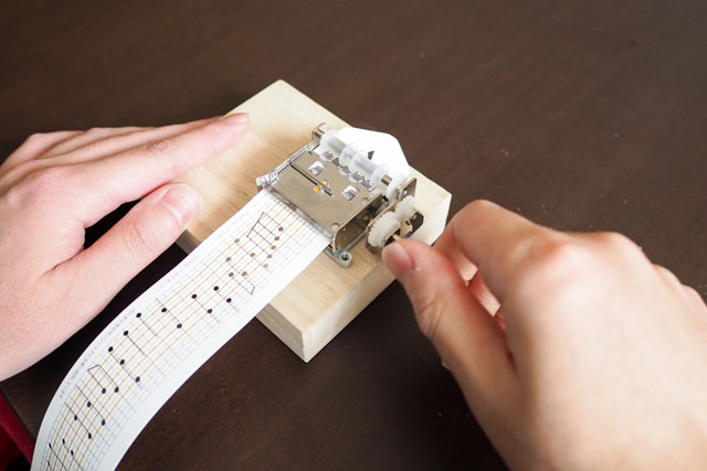 パンチカードはこんな風に読み込ませる。そしてハンドルをぐるぐると手回しすると、紙が送られてオルゴールの音色が聞こえる