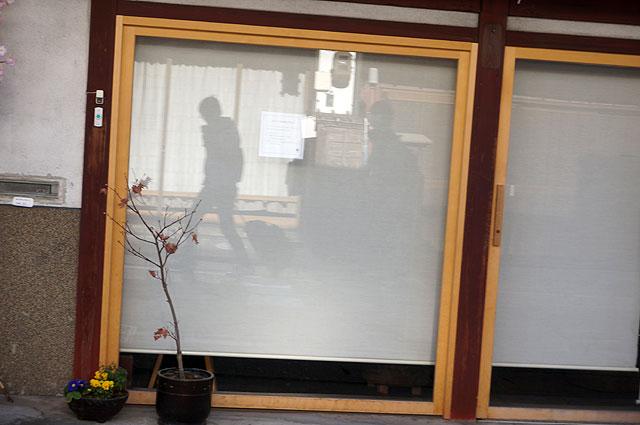 一列になって無言で歩く2人の姿が窓ガラスに映る