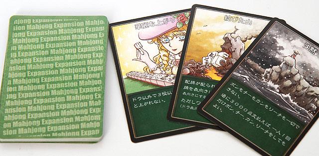 中身はカード。麻雀を打つ時、毎局始めに山札から1枚カードをめくり、そこに書いてある指示に従って(それ以外は普通に)打つ。
