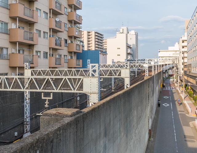 東大島駅から西(都心方向)へ300mほど行ったところから振り返る。高架だった線路は塀に囲われて、このあたりですでに地面より下に。