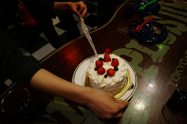 誕生日ケーキを切り始める同僚